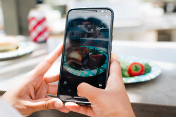 Woman taking photo of food at party with cell phone Wall mural