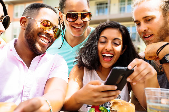 Friends at party laughing at something on cell phone screen.