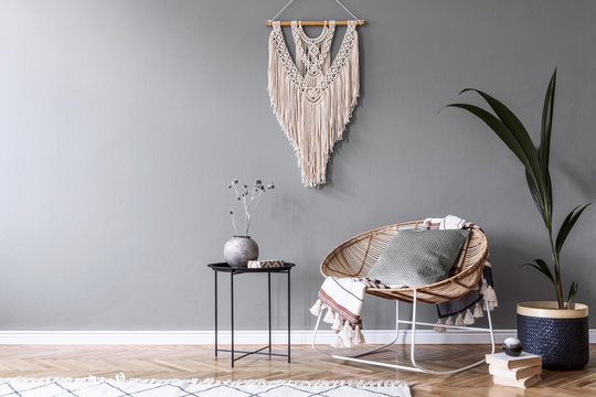 Modern boho interior design of sitting room with design rattan armchair,coffee table, beige macrame, tropical plants and elegant accessories. Stylish home decor.  Template. Copy space. Home staging.