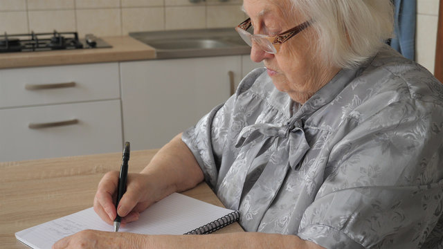 Old woman is writing letter or the last will