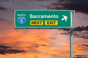 Sacramento California next exit route 5 freeway sign with sunset sky. Wall mural