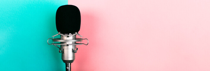 studio microphone on a blue pink background, panoramic mock-up with space for text