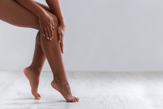 Cropped of female legs, woman touching her skin after waxing