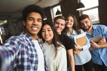 Group selfie of happy international college students