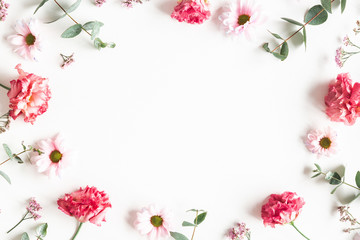 Flowers composition. Frame made of pink flowers and eucalyptus branches on white background....