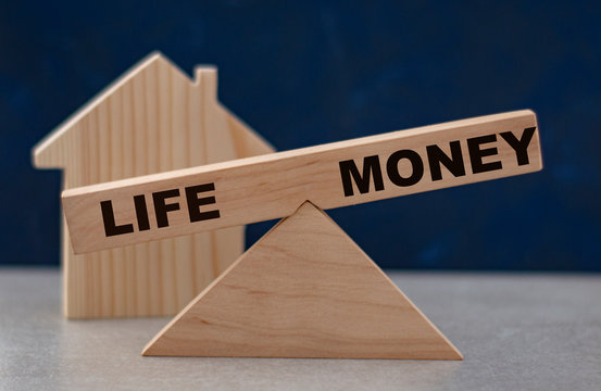conceptual balance between life and money on wooden scales