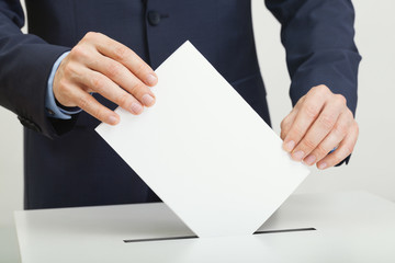 Man in suit holding ballot paper in hand and throwing it into election box