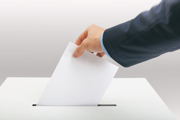 Man in suit holding ballot paper in one hand and throwing it into election box