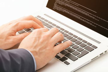 Caucasian male in suit typing something on laptop with code seen on the screen