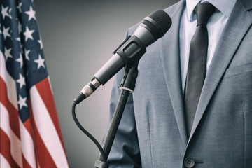 Man in suit standing close to microphone with USA flag on background