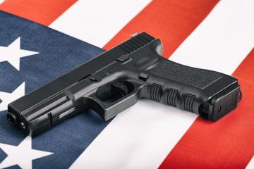 Black handgun over US flag - close up studio shoot