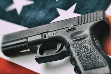 Close up studio shot of a black handgun over US flag