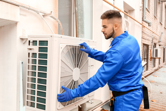 Male technician installing outdoor unit of air conditioner