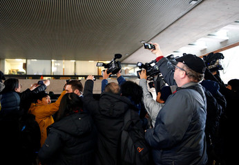 Members of the media crowd around the car of Huawei Chief Financial Officer Meng Wanzhou as she leaves B.C. Supreme Court for a lunch break during the first day of her extradition hearing in Vancouver