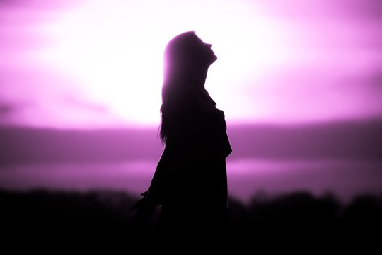 Youth woman soul at pink sun meditation awaiting future times. Silhouette in front of sunset or sunrise in summer nature. Symbol for healing burnout therapy, wellness relaxation or resurrection