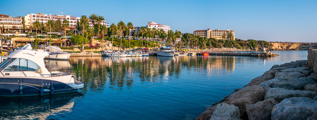 Cyprus coast panorama with yachts, boats, palms on waterfront and hotel buildings. Mediterranean resort for travel and vacation.