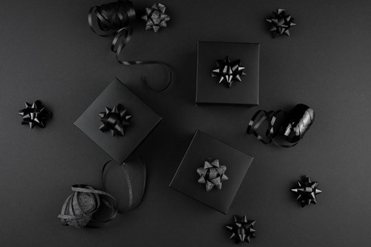 Minimalist black flat lay. Black gift boxes with ribbons on black surface, black friday concept, gift for man, father, husband.