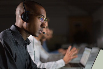 Focused call center operator communicating with client. African American young man in eyeglasses looking at laptop while serving client. Call center concept