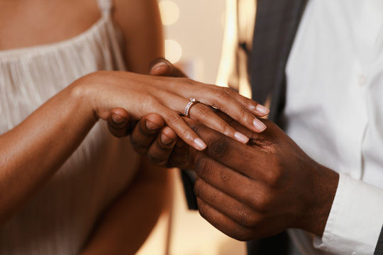 Afro guy putting ring on his girlfriend finger