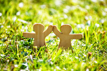 Fotorollo Gelb Wooden little men holding hands. Teamwork, friendship and love concept