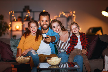 family mother father and children watching projector, TV, movies with popcorn in   evening   at home. Wall mural