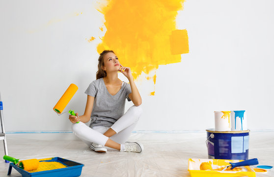 Repair in apartment. Happy young woman paints wall .