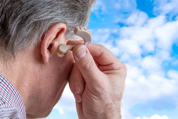 head of a senior man inserts hearing aid in his ear