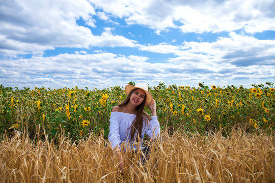 Brunette woman in white blouse sitting on a background of golden wheat and sunflowers fields