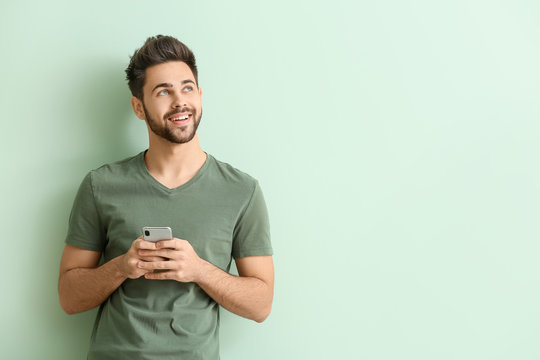 Happy young man with mobile phone on color background