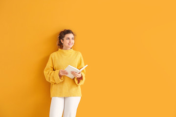Beautiful young woman in warm sweater and with book on color background