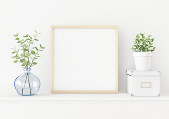 Interior poster mockup with square gold metal frame on the table with plants in blue vase, pot and box on empty white wall background. 3D rendering, illustration.