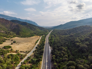Aerial view of highway road in a valley surrounded by mountains. Blue cloudy sky. The hills are covered with green forests. Sardinia, Mediterranean island. Vacation and tourism concept.
