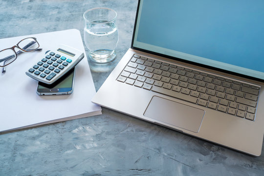 business workspace with accounting  equipment like laptop, calculator, paper and water glass on a blue gray background, copy space, selected focus, narrow depth of field