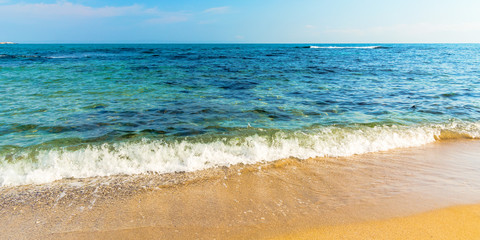 sea scenery in summer. beach with golden sand. wonderful vacation background with transparent calm waves and blue sky. panoramic view