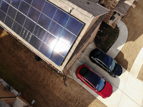 Solar panels on single family home with electric cars in the driveway