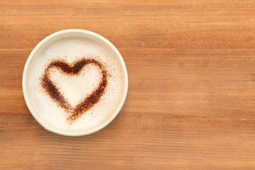 Top view of cup of cappuccino coffee with  heart shaped chocolate powder on brown wooden table