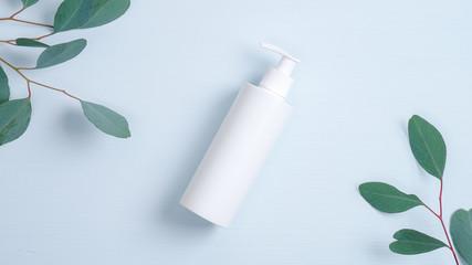 Fototapeta Pump plastic bottle for intimate gel dispenser or liquid soap on blue background with green eucalyptus leaves. Intimate hygiene, cosmetics SPA branding mockup. Flat lay minimalist style composition