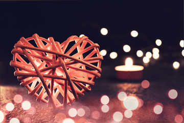 Romantic composition - one wicker heart is a symbol of love, lights and a burning candle on a dark table. Valentines day concept