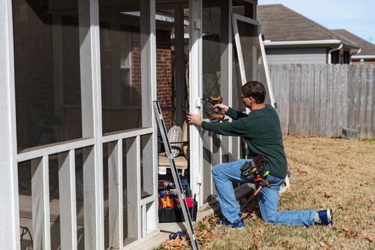 Repairman works on door of back porch