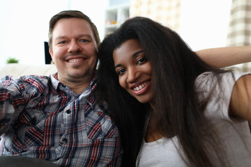 Portrait of cheerful mixed race couple taking happy selfie on sofa indoors. Man and latino woman widely smiling on camera. Multinational and biracial family concept
