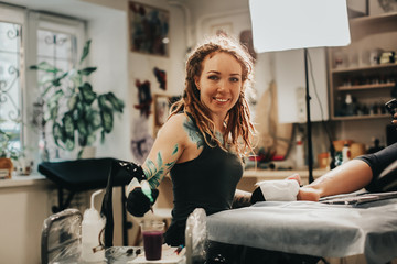Hipster woman with tattoos dreadlocks makes tattoo