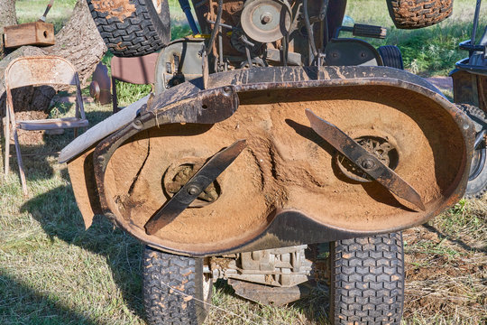 Underside view of old worn out double Lawn Mower Blades on riding lawn mower deck