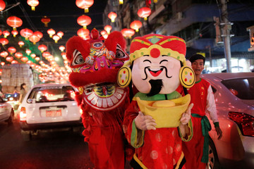 A performer in a fortune god costume and a lion dance crew greet people on the streets ahead of Chiense New Year in Yangon