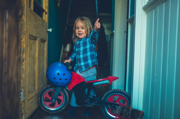 Little toddler with push motorbike giving thumbs up