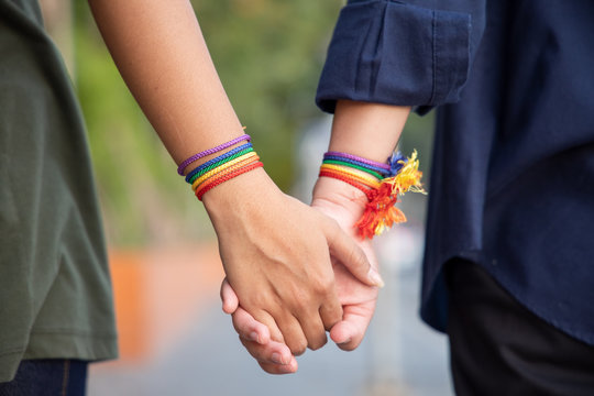 hand of LGBT women holding together with rainbow ribbon symbol; concept of LGBT pride, LGBTQ people, lgbt rights campaign, same sex marriage