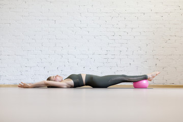 Full body stretching and relax. Beautiful caucasian woman lying on the floor with feet on small fit ball and hands up in loft fitness studio indoor, selective focus.