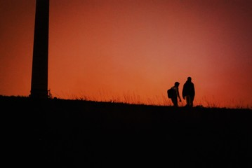 Door stickers Cuban Red Couple walking on a grass covered hill under the red sky