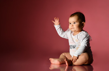 Chubby kid in white bodysuit, barefoot. She is pulling her hands to someone, sitting on floor against pink background. Close up