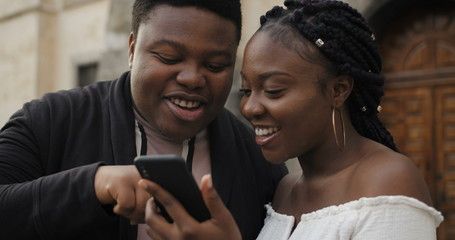 Close up of cheerful couple looking at smartphone screen and laughing. Young african couple standing outdoors using mobilephone, smiling, talking. Concept of people and coomunication.