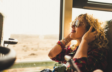 Beautiful blonde adult woman enjoying the travel on bus or train listening music with headphones - wanderlust lifestyle and happy people doing trip - happy people and transport Fototapete